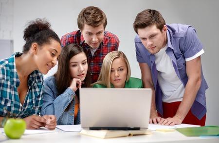 multitud gente: la educación, la gente, la amistad, la tecnología y el concepto de aprendizaje - grupo de estudiantes de secundaria internacionales o compañeros de clase con el ordenador portátil en el aula