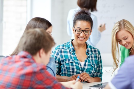 estudiantes de secundaria: la educación, la gente, la amistad, la tecnología y el concepto de aprendizaje - grupo de estudiantes de secundaria internacionales felices o compañeros de clase con el aprendizaje en el aula libro