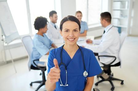 consulta médica: cuidado de la salud, el gesto, la profesión, la gente y concepto de la medicina - médico feliz hembra o enfermera sobre el grupo de médicos reunidos en el hospital muestran los pulgares para arriba gesto Foto de archivo