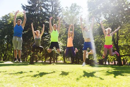 estilo de vida: fitness, esporte, amizade e estilo de vida saudável conceito - grupo de amigos ou desportistas adolescentes feliz que salta altamente ao ar livre