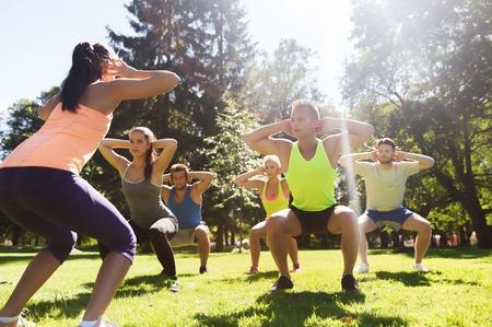 фитнес: фитнес, спорт, дружба и концепции здорового образа жизни - группа подростков друзей или спортсменов, осуществляющих и делать приседания на лагере