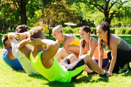 fitness, sport, vriendschap en gezonde levensstijl concept - groep van gelukkige tiener vrienden of sporters trainen en sit-ups op boot camp