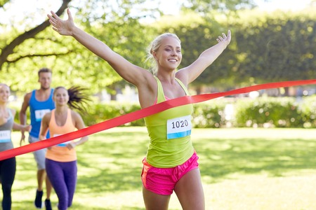 marathon running: fitness, sport, victory, success and healthy lifestyle concept - happy woman winning race and coming first to finish red ribbon over group of sportsmen running marathon with badge numbers outdoors