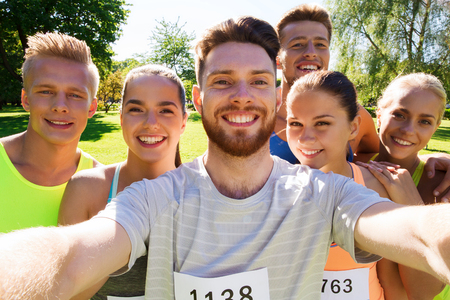 fitness, sport, friendship, technology and healthy lifestyle concept - group of happy teenage friends with racing badge numbers taking selfie by smartphone at marathon outdoors Фото со стока