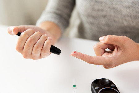 medicine, diabetes, glycemia, health care and people concept - close up of woman checking blood sugar level by glucometer at home