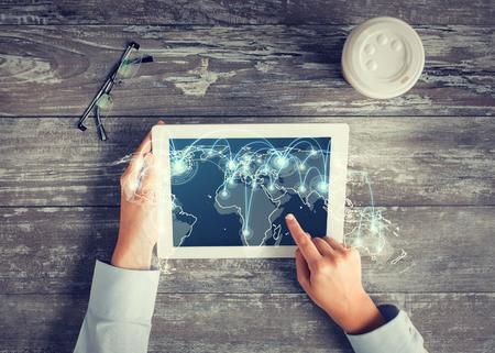 het bedrijfsleven, mensen, internationale communicatie, de locatie en technologie concept - close-up van de handen wijzende vinger op de computer screen tablet pc met een kaart van de wereld en het netwerk op lijst
