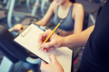sport, fitness, lifestyle, technology and people concept - close up of trainer hands with clipboard writing and woman working out on exercise bike in gym Reklamní fotografie - 49090294