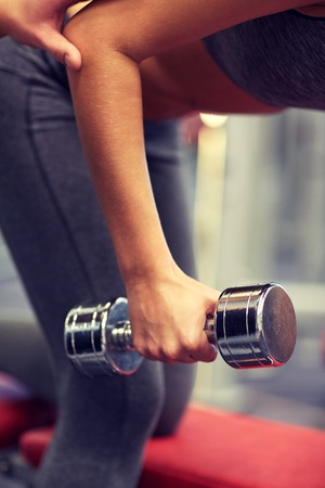 personal trainer: fitness, sport, exercising and weightlifting concept - close up of young woman and personal trainer with dumbbells flexing muscles in gym