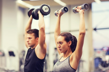 lift hands: sport, fitness, lifestyle and people concept - smiling man and woman with dumbbells flexing muscles in gym