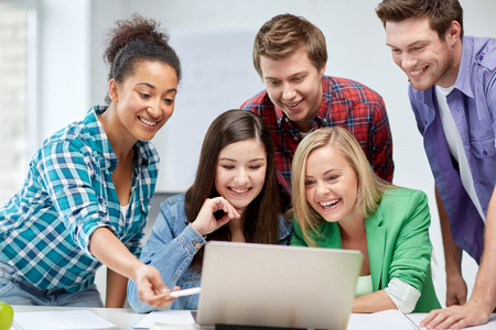education, people, friendship, technology and learning concept - group of happy international high school students or classmates with laptop computer in classroom