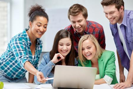 estudiantes de secundaria: la educación, la gente, la amistad, la tecnología y el concepto de aprendizaje - grupo de estudiantes de secundaria internacionales felices o compañeros de clase con el ordenador portátil en el aula