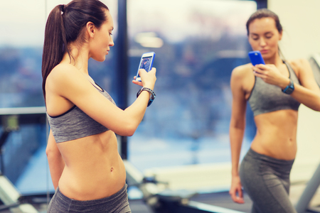 fit: sport, fitness, lifestyle, technology and people concept - young woman with smartphone taking mirror selfie in gym