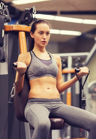 girl sport: sport, fitness, lifestyle and people concept - young woman flexing muscles on gym machine Stock Photo
