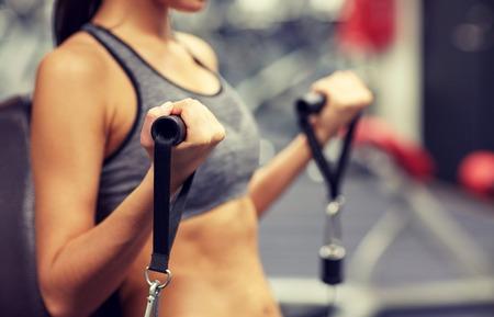 スポーツ、フィットネス、ライフ スタイル、人々 の概念 - ケーブルのジムのマシンでの筋肉がうごめくの若い女性のクローズ アップ