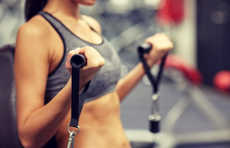 girl in sportswear: sport, fitness, lifestyle and people concept - close up of young woman flexing muscles on cable gym machine Stock Photo