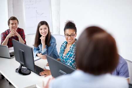 multiracial: education, people, technology and learning concept - group of happy international high school students and teacher in computer class Stock Photo