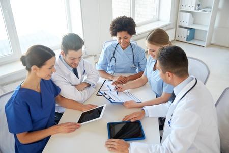 doktor: szpital, edukacja medyczna, opieka zdrowotna, ludzie i medycyna koncepcji - grupa szczęśliwych lekarzy z komputerów Tablet PC spotkania w gabinecie lekarskim