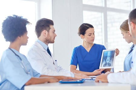 spine surgery: profession, people, surgery, radiology and medicine concept - group of doctors with x-ray on tablet pc computer screen meeting at medical office Stock Photo