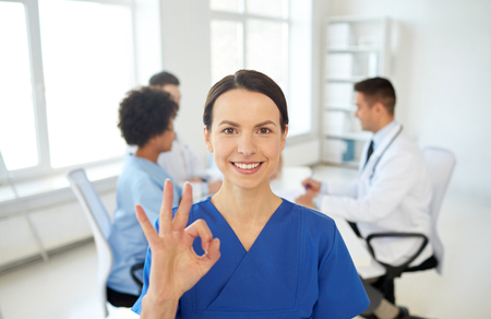medics: health care, gesture, profession, people and medicine concept - happy female doctor over group of medics meeting at hospital showing ok hand sign