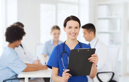 medics: clinic, profession, people and medicine concept - happy female doctor with clipboard over group of medics meeting at hospital