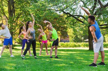 boot camp: fitness, sport, friendship and healthy lifestyle concept - group of happy teenage friends or sportsmen exercising and stretching hands at boot camp