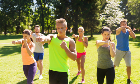 boot camp: fitness, sport, martial arts, self-defense and healthy lifestyle concept - group of teenage friends or sportsmen exercising and at boot camp
