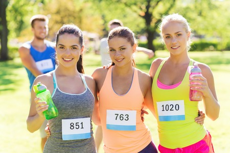 young woman smiling: fitness, sport, friendship, marathon and healthy lifestyle concept - happy young sporty women with racing badge numbers and water bottles outdoors Stock Photo