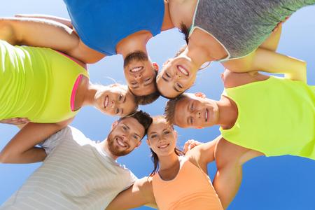 fitness, sport, vriendschap en gezonde levensstijl concept - groep van gelukkige tiener vrienden of sporters in cirkel buitenshuis