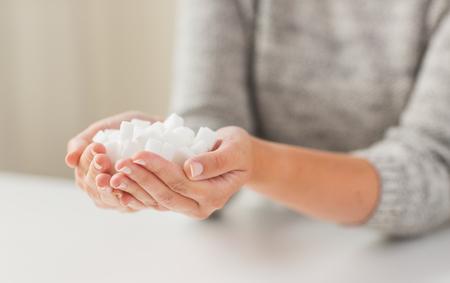 음식, 정크 푸드, 당뇨병과 건강에 해로운 먹는 개념 - 여자 손에 흰색 덩어리 설탕의 닫습니다 스톡 콘텐츠 - 49090174
