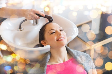 woman washing hair: beauty and people concept - happy young woman with hairdresser washing head at hair salon Stock Photo