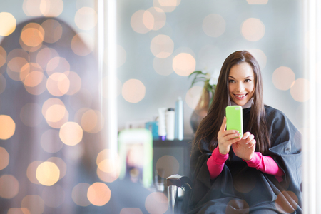 beauty and people concept - happy young woman with smartphone taking mirror selfie at hair salon Stock Photo