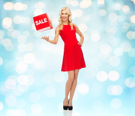 sale sign: people, shopping, discount and holidays concept - smiling woman in red dress holding cardboard box with sale sign over blue lights background