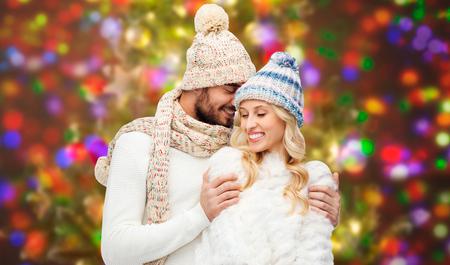 parejas: invierno, la moda, de pareja, de la navidad y la gente concepto - hombre sonriente y la mujer en sombreros y abrazos bufanda sobre las vacaciones luces de fondo