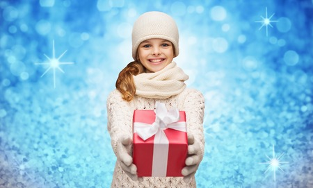 muffler: christmas, winter, holidays and childhood concept - smiling girl in hat, muffler and gloves with gift box over blue glitter or lights background