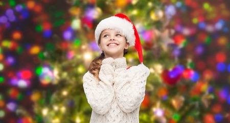 happy christmas: christmas, winter, holidays and childhood concept - dreaming girl in santa helper hat over glitter or lights background