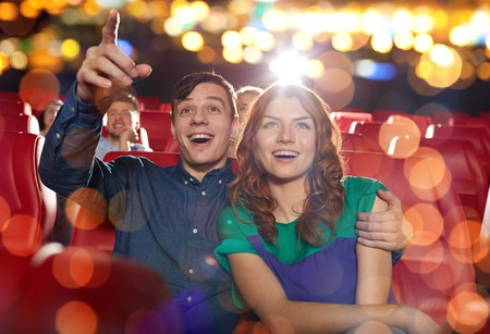 spectator: cinema, entertainment, gesture, emotions and people concept - happy friends watching movie pointing finger to screen in theater Stock Photo