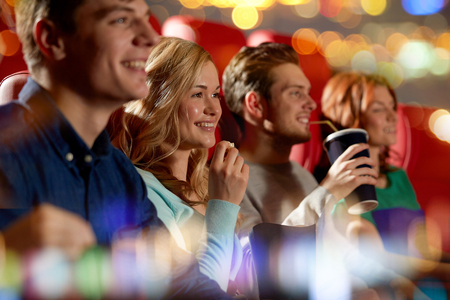 eating popcorn: cinema, entertainment and people concept - happy friends watching movie in theater