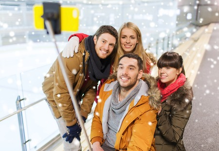 stick: people, friendship, technology and leisure concept - happy friends taking picture with smartphone selfie stick on skating rink
