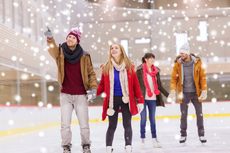 iceskates: people, friendship, sport, gesture and leisure concept - happy friends pointing finger on skating rink