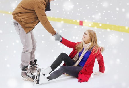 women friendship: people, friendship, sport and leisure concept - smiling man helping women to rise up on skating rink