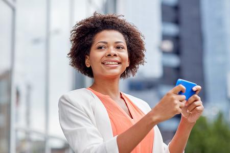 mujer trabajadora: negocios, la tecnolog�a, la comunicaci�n y el concepto de la gente - joven sonriente africano americano de negocios con el tel�fono inteligente en la ciudad Foto de archivo