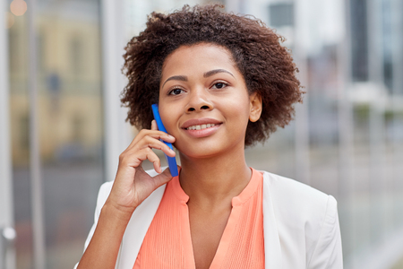 elegant woman: business, communication, technology and people concept - young smiling african american businesswoman calling on smartphone in city