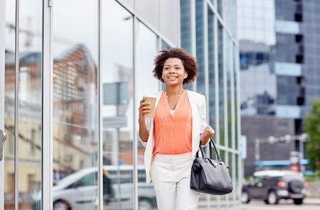 Unternehmen und Menschen Konzept - junge l�chelnde Afroamerikanergesch�ftsfrau mit Kaffeetasse in der Stadt Lizenzfreie Bilder