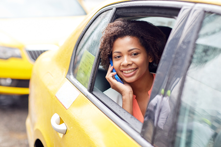 mobile communication: business trip, transportation, travel, gesture and people concept - young smiling african american woman calling on smartphone in taxi at city street