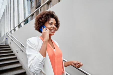 woman stairs: business, communication, technology and people concept - young smiling african american businesswoman calling on smartphone going down stairs into city underpass