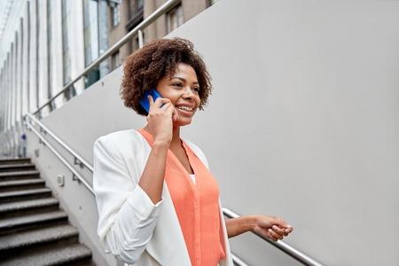 mujeres negras: negocio, la comunicaci�n, la tecnolog�a y el concepto de la gente - joven sonriente africano americano de negocios que invita al tel�fono inteligente bajar escaleras en paso subterr�neo de la ciudad Foto de archivo