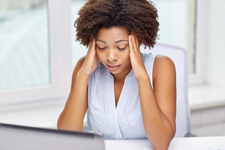 教育、ビジネス、失敗、技術コンセプト - アフリカ系アメリカ人実業家またはラップトップ コンピューターとオフィスで紙と学生