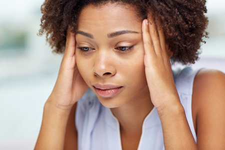 female face: people, emotions, stress and health care concept - unhappy african american young woman touching her head and suffering from headache
