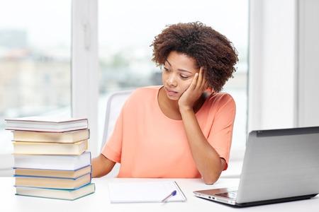 persone nere: le persone, la tecnologia e il concetto di istruzione - annoiato African American giovane donna seduta al tavolo con computer portatile, libri e blocco note a casa