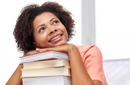 nice girl: education, school, knowledge and people concept - happy smiling african american student girl with books sitting at table and dreaming at home